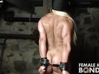 Il bodybuilder femminile nudo lotta nelle restrizioni